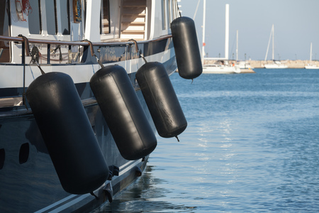Black rubber inflatable ship fenders hanging above sailing yacht hull