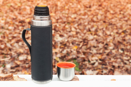 Stainless steel vacuum tourist thermos stands on white table in autumn park