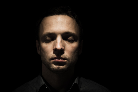 Closeup studio face portrait of young adult European man with closed eyes isolated over black background, low key photo Stock Photo