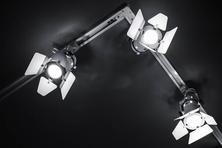 Three spot lights in metal body over black ceiling background, stage illumination equipment