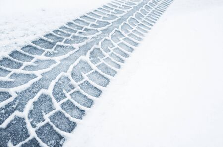 Car track on a wet snowy road, closeup background photo texture Standard-Bild