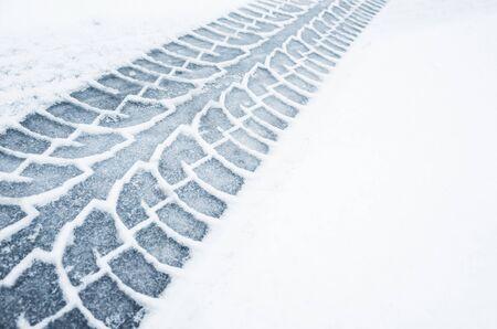 Car track on a wet snowy road, closeup background photo texture Foto de archivo