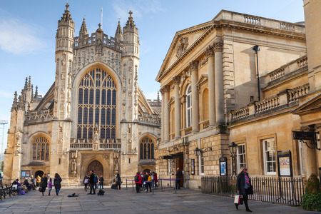 Bath, United Kingdom - November 2, 2017: The Abbey Church of Saint Peter and Saint Paul, Bath, commonly known as Bath Abbey. Ordinary people walk on city square