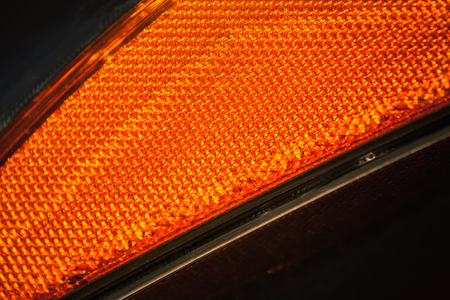 Modern car headlight fragment, orange cataphyte pattern