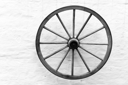 Old wooden cart wheel hanging on rural wall, black and white