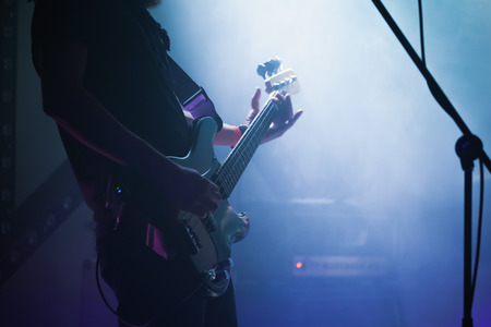 Live rock music background, electric bass guitar player in blue smoke, closeup photo with soft selective focus