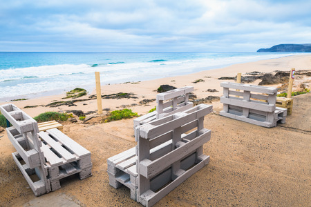 Standard white wooden furniture made of cargo pallets, seaside bar terrace. Porto Santo island, Madeira archipelago, Portugal Stock Photo