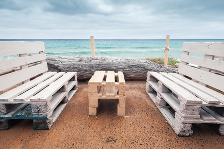 Standard wooden furniture made of cargo pallets, cheap seaside terrace on Porto Santo island, Madeira archipelago, Portugal