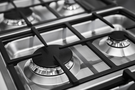Modern gas stove burners made of shiny stainless steel and cast iron