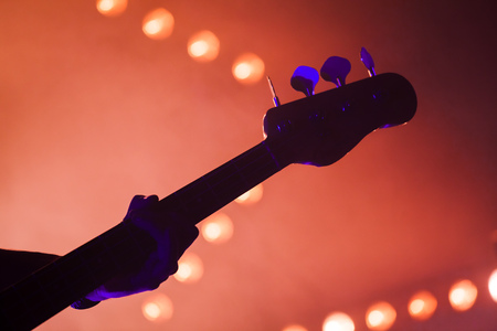 Electric bass guitar player over bright blurred stage lights, close-up silhouette photo with soft focus