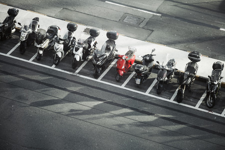 Genova, Italy - January 18, 2018: Vintage red Vespa scooter stands between modern black and white motorbikes