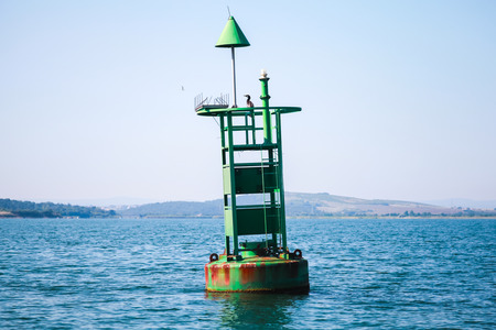 Green navigation buoy with cone topmark floats on sea water. Bay of Burgas, Black Sea, Bulgaria
