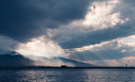 Dark stormy clouds with sunbeams, landscape background photo, bay of Izmir city, Turkey Reklamní fotografie