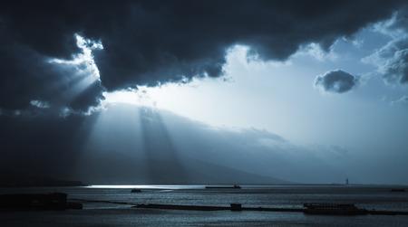 Dark stormy clouds and sunlight, landscape background photo. Cargo ships enter bay of Izmir, Turkey. Blue toned stylized photo