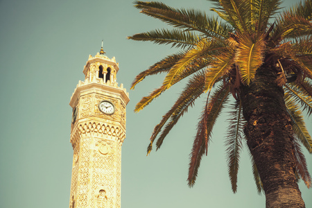 Clock tower and palm tree on Konak Square. It was built in 1901 and accepted as the official symbol of city Izmir, Turkey. Vintage toned photo