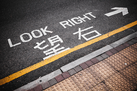 Look right. Caution road marking for pedestrians shows direction of approaching traffic in Hong Kong city