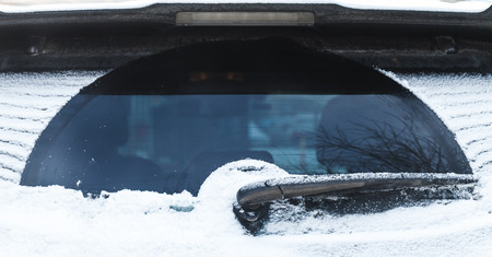 Car wiper on rear SUV window covered with snow in cold winter season Stock Photo
