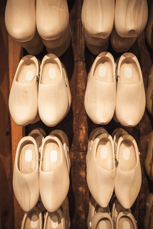 Uncolored new clogs made of poplar wood hanging in souvenir shop. Klompen are traditional Dutch shoes for everyday use