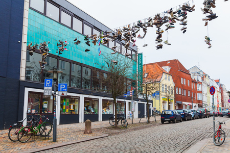 Flensburg, Germany - February 10, 2017: Abandoned sporty shoes hang on electric wire, street view of old Flensburg, Germany Redakční