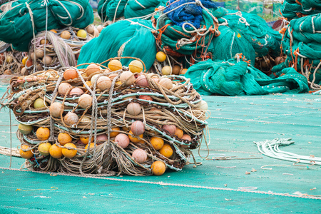 Drying fishing nets with orange floats lay on the sea coast in port of Busan. South Korea