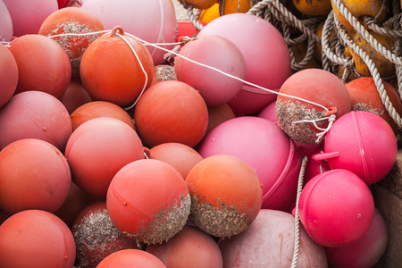 Red spherical plastic floats of fishing nets lay in port Stock Photo