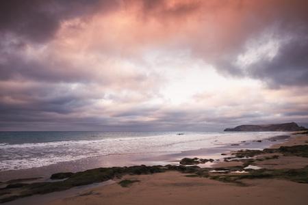Wet coastal stones with seaweed under dramatic cloudy sky on the beach of Porto Santo island, Madeira archipelago, Portugal