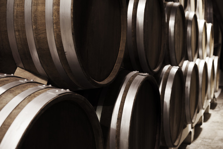 Wooden barrels in winery, close up photo with selective focus