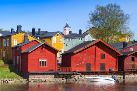 Porvoo town, Finland. Old red wooden houses on the river coast in sunny day