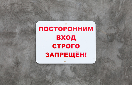 White plate on gray concrete wall with the inscription in Russian: Unauthorized entry is strictly prohibited