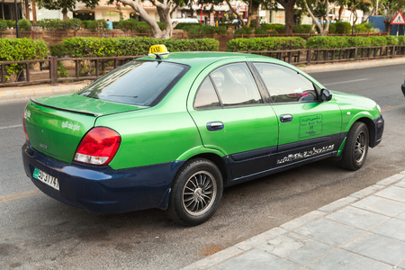 Aqaba, Jordan - May 18, 2018: Green taxi car stands parked on a street side in Aqaba city, rear view