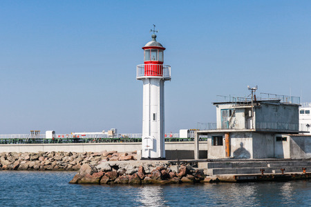 White lighthouse tower with red top stands on the entrance breakwater in Burgas port, Black Sea coast, Bulgaria