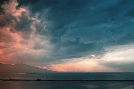 Colorful dramatic sky with red sunlight over sea. Izmir bay landscape, Turkey