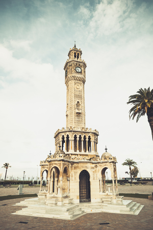 Historical clock tower on Konak Square. it was built in 1901 and accepted as the official symbol of Izmir City, Turkey/ Vintage toned vertical photo