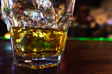 Whiskey with ice in a glass stands on the bar. Close-up photo with soft selective focus