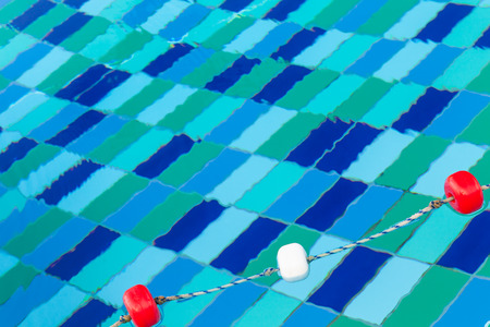 Red and white plastic floats on rope, swimming pool background Banco de Imagens