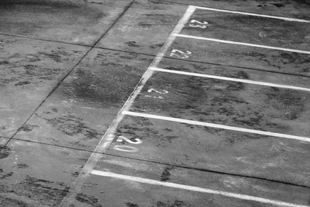 Ferry terminal loading port area, road marking with lane numbers and dividing lines on dirty gray asphalt