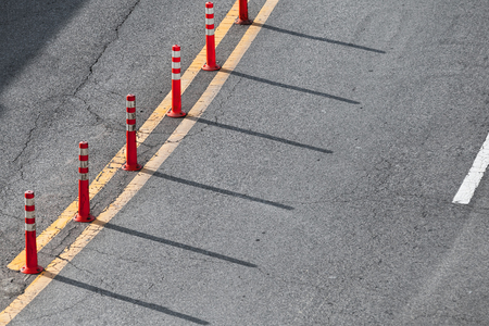 Yellow double dividing line and red plastic warning poles over gray highway asphalt