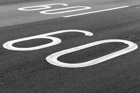 60 km per hour. Speed limit road marking on dark gray asphalt