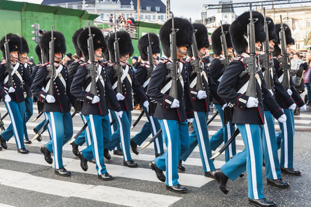 Copenhagen, Denmark - December 9, 2017: The procession of the royal guardsmen to the royal palace Amalienborg, accompanied by the orchestra. The ceremony of changing the guard of honor in Copenhagen Editorial