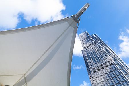 Foto di sfondo astratto architettura moderna, torre di uffici in vetro e acciaio vicino alla tenda a forma di vele