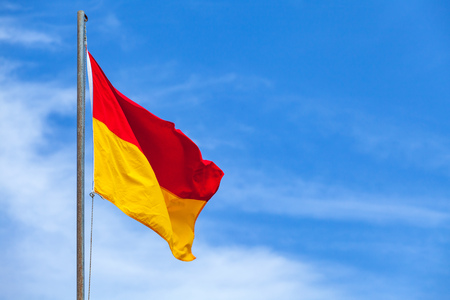 Red and yellow flag on a beach over blue sky background Stock Photo