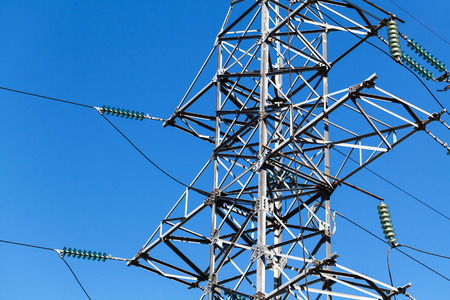 Lattice-type steel tower fragment over blue sky as a part of high-voltage line. Overhead power line details Stock Photo