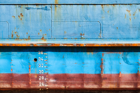 Blue cargo ship hull with red waterline and draft marks, front view, background texture