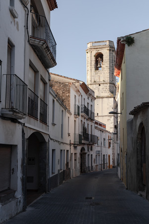 Calafell, Spain - August 15, 2014: Street view with catholic cathedral in old town of Calafell. Tarragona region, Catalonia, Spain