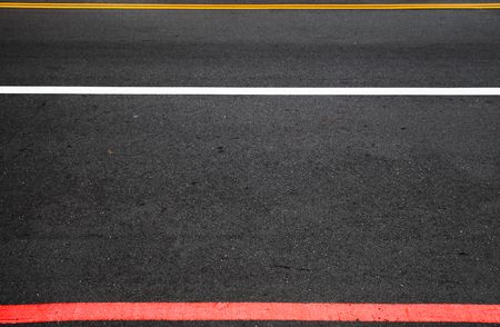 Highway road marking. Yellow, white and red lines over dark asphalt. Background photo Imagens