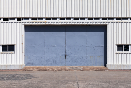 Closed blue gate in white ridged metal warehouse wall, flat background photo texture