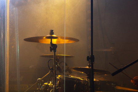Live rock music photo background, rock drum set  with cymbals in warm stage lights. Close-up photo, soft selective focus Stockfoto