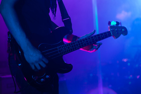 Live rock music background, bass guitar player on a stage, close-up photo with soft selective focus Reklamní fotografie