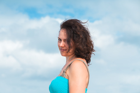 Smiling young adult Caucasian woman in blue dress, outdoor portrait over cloudy sky