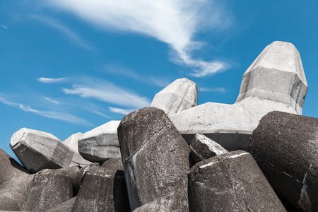 Gray breakwater blocks made of concrete are under cloudy sky. Industrial background photo